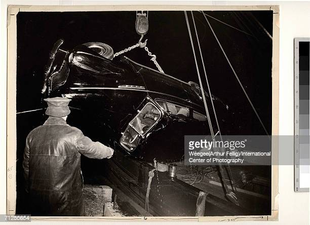 A policeman in rain gear points as a crane on a barge recovers a car which contains at least one dead body from the East River New York late 1930s...