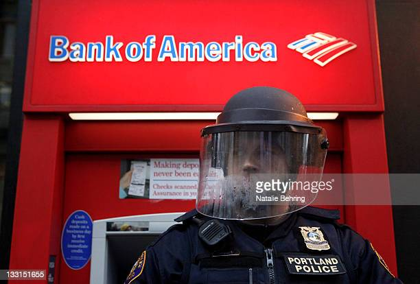 A policeman in riot gear defends a Bank of America as protesters march past various banks November 17 2011 in Portland Oregon The Occupy Portland...