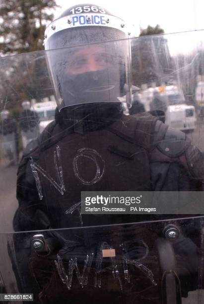 A policeman in riot gear stands at the entrance to Hillsborough village near Belfast to prevent peace protesters from reaching Hillsborough Castle...