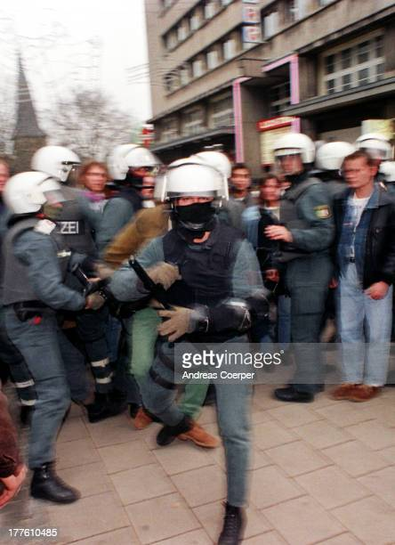 Policeman in riot-gear attacks the photo-journalist shooting the situation. The photograph is not digitally manipulated but shot on long-time...