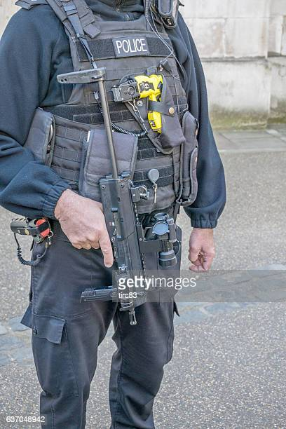 policeman in uniform with many weapons - police taser stock pictures, royalty-free photos & images