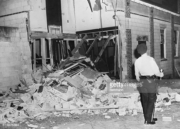 Policeman inspects the blast shattered exterior of the Bell Street Baptist Church in Montgomery in Alabama on January 10, 1957 after the church and...