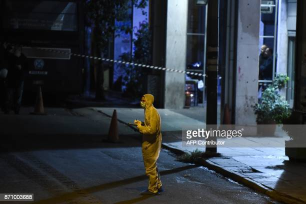 A policeman inspects the street after a gunman fired riot police guarding the headquarters of the Greek Socialist Party Pasok in Athens on November 6...