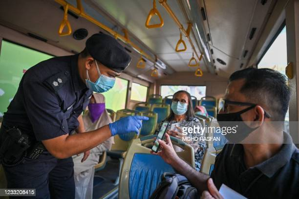 Policeman inspects the travel documents of a passenger on a bus at a roadblock during the nationwide lockdown, amid fears over the spread of the...