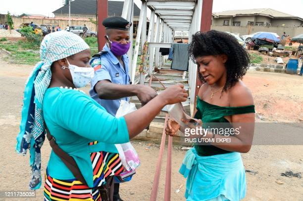 Policeman instructs a lady to wear face mask at a checkpoint in compliance with state directive to curb the spread of COVID-19 coronavirus at...