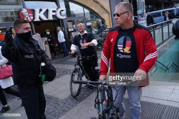 A policeman instructs men wearing QAnon conspiracy shirts to move along during scattered protests at Alexanderplatz against lockdown measures and...