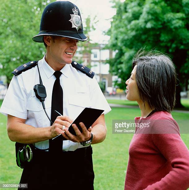 policeman interviewing woman in street, smiling - victim stock pictures, royalty-free photos & images