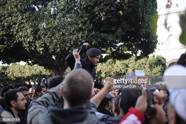 A policeman is carried on the shoulders of demonstrators during protests on January 21 in Tunis Tunisia began national mourning today for the dozens...