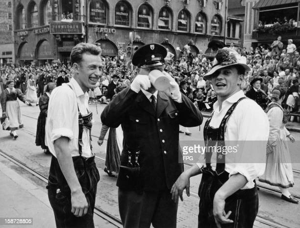 A policeman is happy to join two Bavarians in a mug of German beer during the Oktoberfest celebrations in Munich Germany 24th September 1958