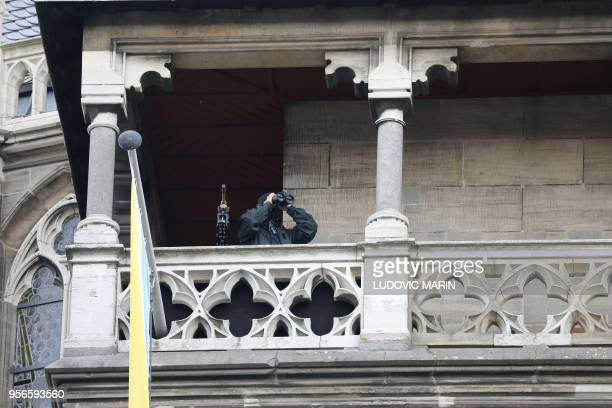 A policeman is looking with binoculars from the top of the cathedral ahead the arrival of French President Emmanuel Macron in Aachen on May 9 one day...
