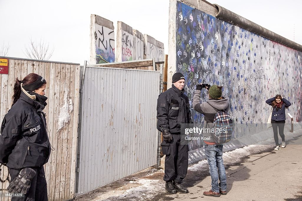 A policeman is photographed by a man as he stands guard next to a section of the Berlin Wall which has been removed to make way for a luxury apartments development on March 27, 2013 in Berlin, Germany. Activists are seeking to stop a stretch of the Berlin Wall, known as the East Side Gallery, from being developed on by a real estate development company. A previous attempt by the developer to remove approximately 25 meters of the wall sparked protests that led to minor clashes with police. Negotiations had been underway and city officials had even offered the developer an alternative property, though removal continued today unannounced and to the surprise of opponents. The East Side Gallery is over one kilometer long and is among the city's biggest tourist attractions.