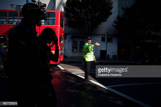 Policeman is regulating the traffic during Notting Hill Carnival at Notting Hill Gate road. London, August 2010.