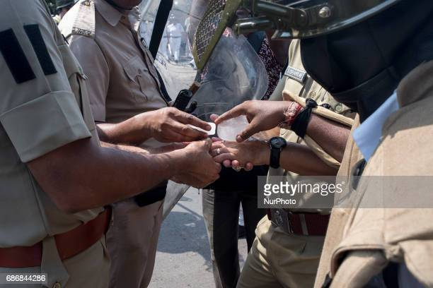 A policeman is rubbing ice on one of their colleague's hand who got injured while managing the violent mob Kolkata India 22 May 2017 After the...