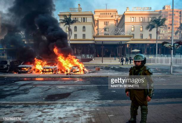 Policeman is seen near cars burning in flames outside the Hotel O'Higgins after being set on fire by demonstrators during a protest against Chilean...