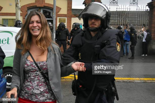 A policeman is seen taking away a woman during the protest against spanish policemen National Police entered by force in the High School of...