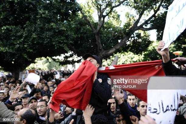 A policeman kisses the Tunisian national flag as demonstrators hold him up by his shoulders during a demonstration in Tunis on January 21 2011...