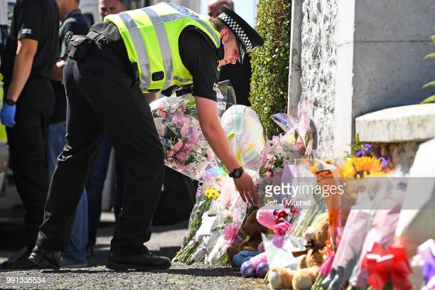 A policeman lay flowers for a member of the public at a house on Ardbeg Road on the Isle of Bute following the conformation that six year old...