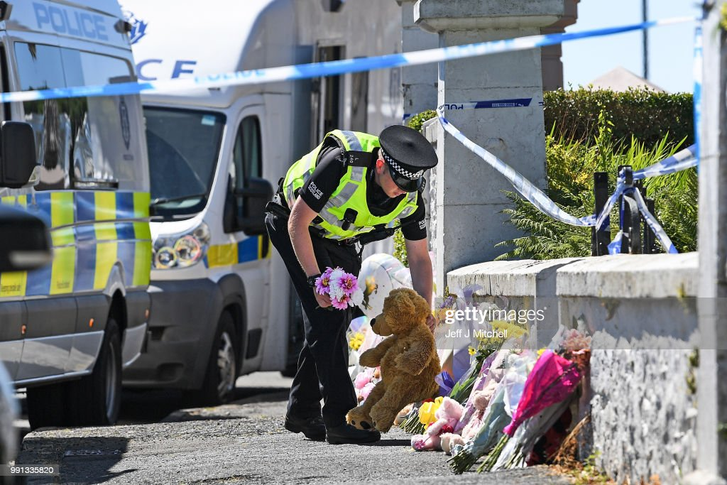 A policeman lay flowers for a member of the public at a house on Ardbeg Road on the Isle of Bute following the conformation that six year old schoolgirl Alesha MacPhail was murdered on July 4, 2018 in Rothesay, Isle of Bute, Scotland.The case has become a murder inquiry yesterday evening following the post-mortem examination on the six year old, police have yet to confirm how she died.