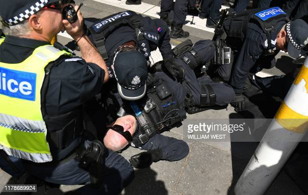 A policeman lays injured on the ground as climate change protesters disrupt the International Mining and Resources Conference being held in Melbourne...