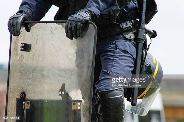 A policeman leaning on his shield