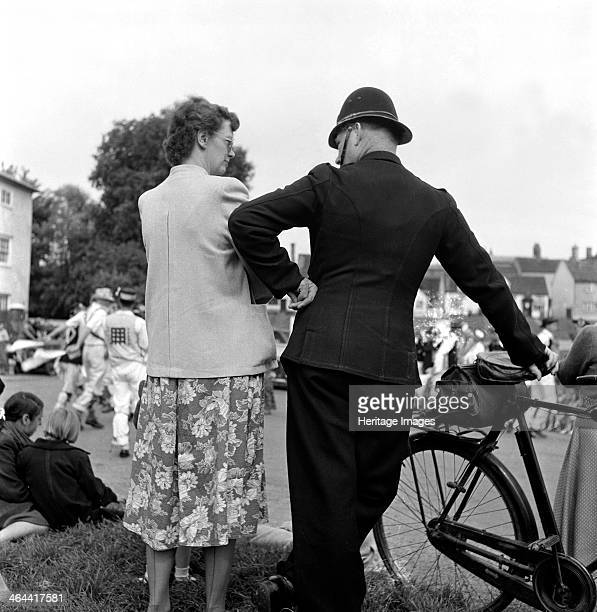 A policeman leans on his bicycle whilst talking to a lady at Finchingfield Village Fair Essex 1958