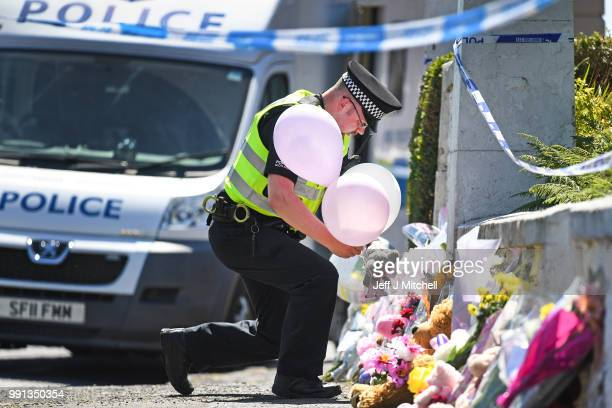 A policeman leaves balloons for a member of the public at a house on Ardbeg Road on the Isle of Bute following the conformation that six year old...