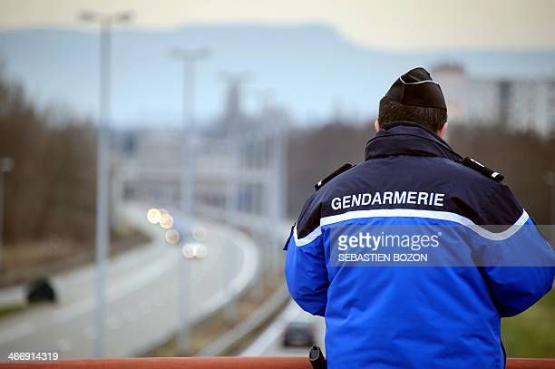 Policeman look at cars on a highway on February 1, 2014 in Saint-Louis next to the France-Switzerland border. AFP PHOTO / SEBASTIEN BOZON