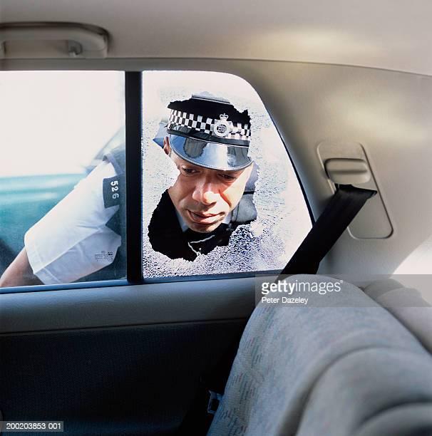 Policeman looking through broken window into back of car