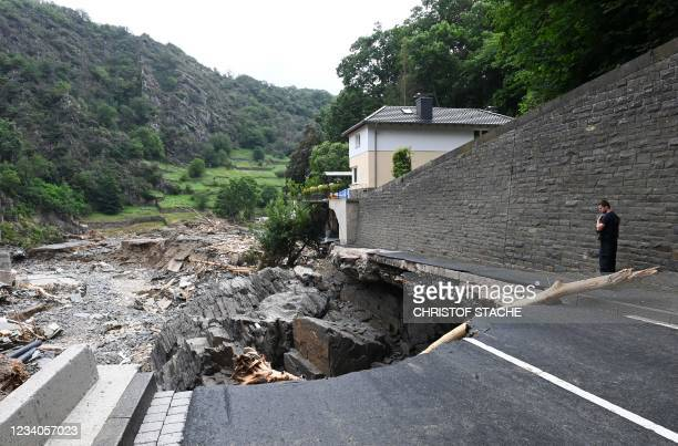 Policeman looks at a piece of road that has sunken in the city of Altenahr, Rhineland-Palatinate, western Germany, on July 19 after devastating...
