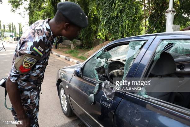 A policeman looks at car vandalised by supporters of an imprisoned leader of the Islamic Movement of Nigeria Ibrahim Zakzaky around the national...