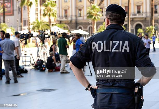 A policeman looks medias in front of the Cassation building during the supreme court session to decide whether to confirm a oneyear prison sentence...