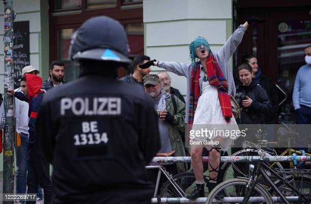 A policeman looks on as a woman sings during scattered leftwing protests in Kreuzberg district on May Day during the novel coronavirus crisis on May...