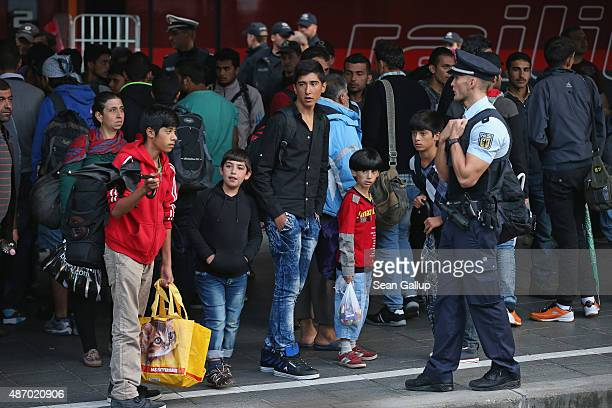 A policeman looks on as mgrants who had arrived on a train from Hungary transfer to a chartered commuter train at Munich Hauptbahnhof main railway...