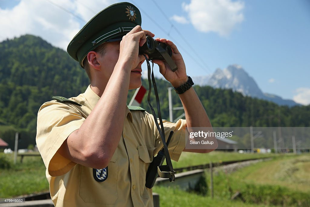 A policeman looks through binoculaurs as the Bavarian Alps stand behind two days before the summit of G7 leaders on June 5, 2015 in Garmisch-Partenkirchen, Germany. G7 leaders will meet at nearby Schloss Elmau on June 7-8 and at least 17,000 police members are on hand to safeguard security at the summit.