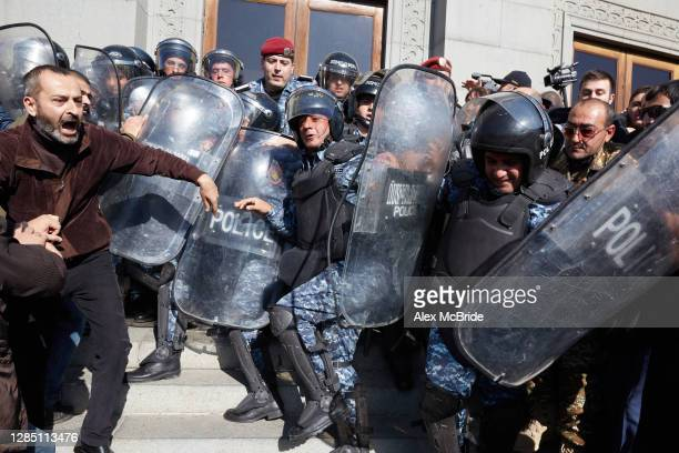 Policeman loses his balance during a tussle as protesters demand the removal of Armenian Prime Minister Nikol Pashinyan from office in Freedom Square...
