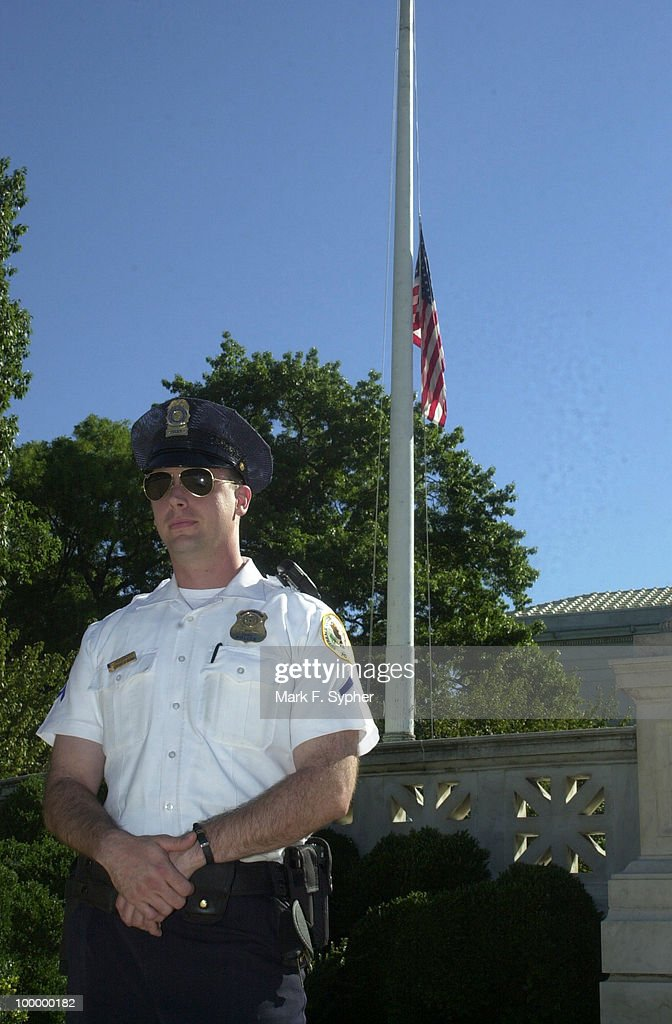 Policeman Mackie stands guard at the U.S. Supreme Court in front of a flag at half-mast.