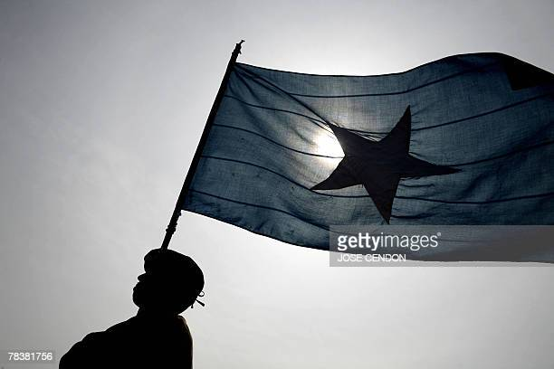 Policeman marches holding a Somali flag during a parade in Mogadishu, 11 December 2007. A roadside blast on Tuesday killed three people, including a...