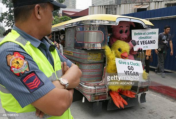 A policeman monitors as activists from the group People for the Ethical Treatment of Animals dressed in animal costumes display placards from the...