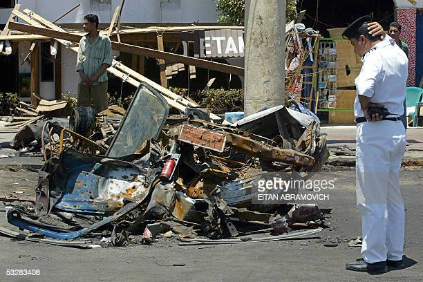 A policeman observes the remains of a car destroyed during a bomb blast in the Red Sea resort town of Sharm ElSheikh 500 kilometers east of Cairo in...