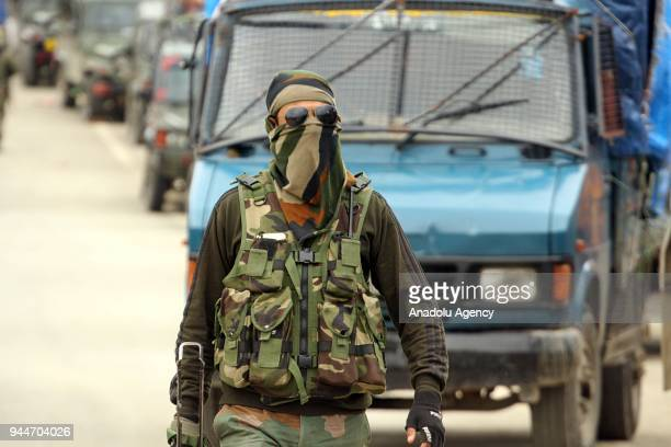 A policeman of Special Operation Group walks near the gunbattle site in Khudwani area of south Kashmir's Kulgam some 60 kilometers from Srinagar the...