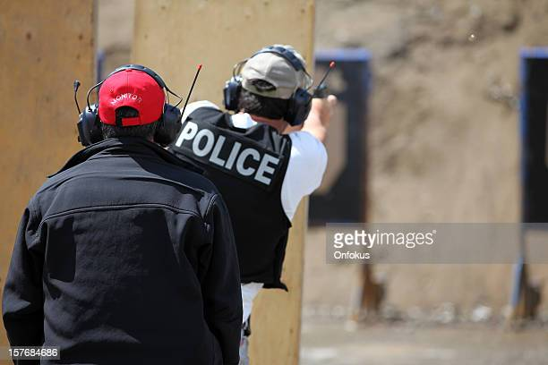 policeman officer shooting 9mm handgun with instructor - ammunition stock pictures, royalty-free photos & images