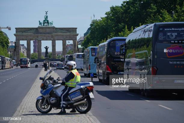 Policeman on a motorcycle watches honking tour buses participating in a protest near the Brandenburg Gate during the coronavirus crisis on May 27,...
