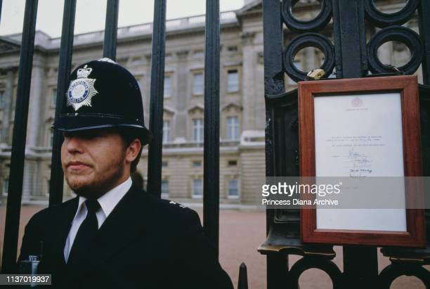 A policeman on duty outside Buckingham Palace next to the official bulletin announcing the birth of Prince Harry to Princess Diana and Prince Charles...