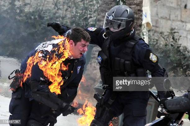 A policeman on fire is helped by a colleague during clashes with demonstrators in central Athens on February 23 2011 Police fired tear gas near the...