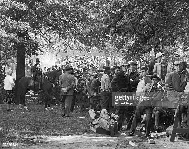 A policeman on horseback keeps a watchful eye on Pittsburgh Pirates fans as they wait standing sitting and lying down in line as they have done all...