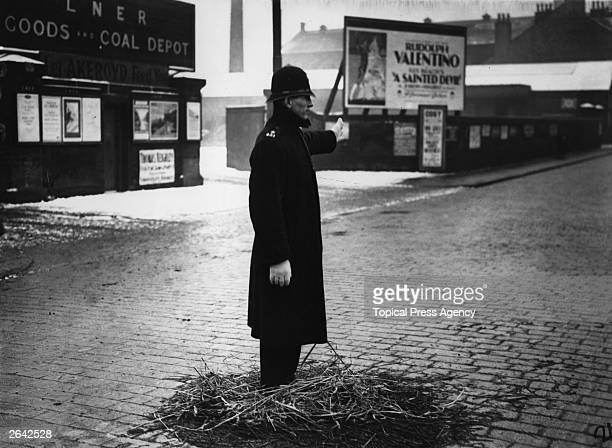 A policeman on point duty in Yorkshire standing on a pile of straw to keep his feet warm