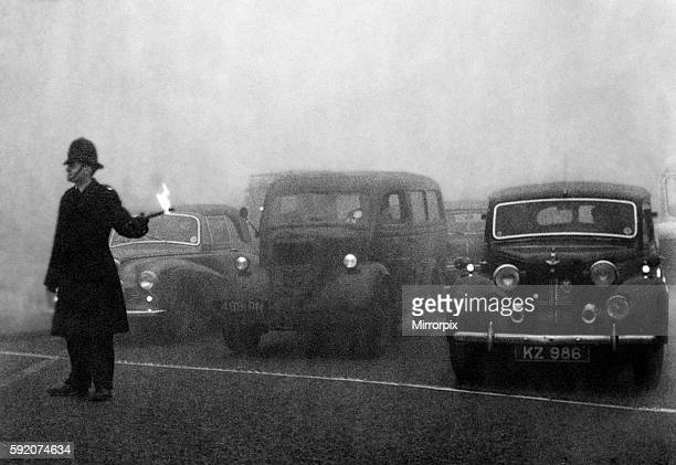 Policeman on point duty seen here using flares to guide the traffic during a heavy smog in London 8th December 1952
