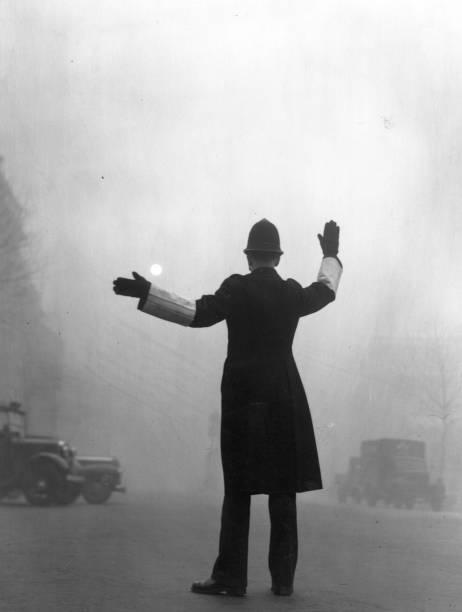 A policeman on traffic duty on a foggy day in Fleet...