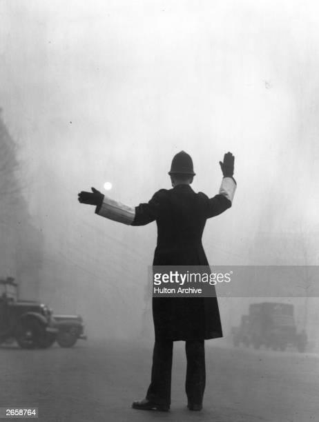A policeman on traffic duty on a foggy day in Fleet Street London