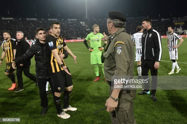 A policeman orders AEK defender Vassilis Lampropoulos and other players to leave the pitch during incidents following the referee's decision to...